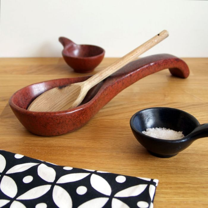 This lovely tamarind-coloured spoon rest is hand made in Indonesia using centuries-old traditional pottery skills.    Resting your kitchen spoons on a spoon rest helps keep your kitchen counter neat and tidy.    Made of solid earthenware by hand and glazed in natural materials, it has a rustic feel, and the colours go beautifully with all kinds of kitchen worktops.    This product is made in Lombok, Indonesia, by potters working with the fair trade co-operative, Lombok Pottery Centre.