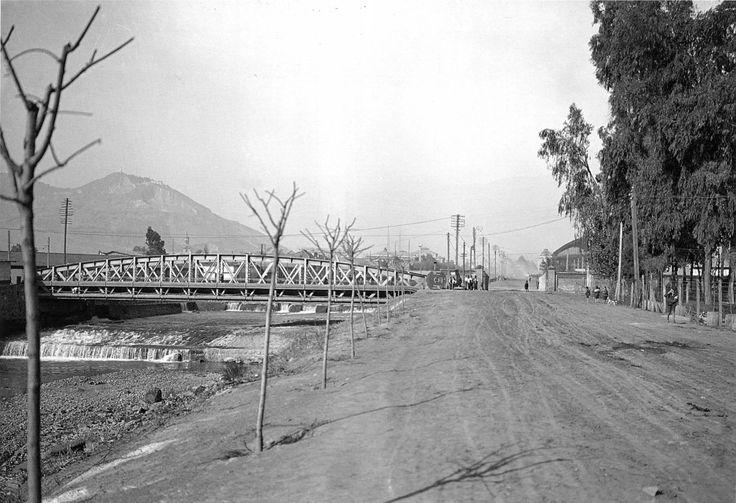 Vista de la ribera sur del Río Mapocho y el Puente Manuel Rodríguez en 1928. Al fondo a la derecha se alcanza a ver la Estación Mapocho en su cara posterior. A la izquierda el Cerro San Cristóbal y su antigua cantera.  Archivo Chilectra.