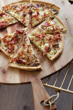Een klassieker uit de Elzas:flammkuchen met crème fraîche, ui en spekjes. Deze zie je vaakals een vierkante, ovalen of rechthoekige plaatpizza, maar wij waren rebels en baktenlekker een rond exemplaar. Verwarm je oven voor op 230 graden en zet je pizzaplaat of bakplaat erin, zodat deze alvast heet kan worden. Leg de pizzabodem op een …