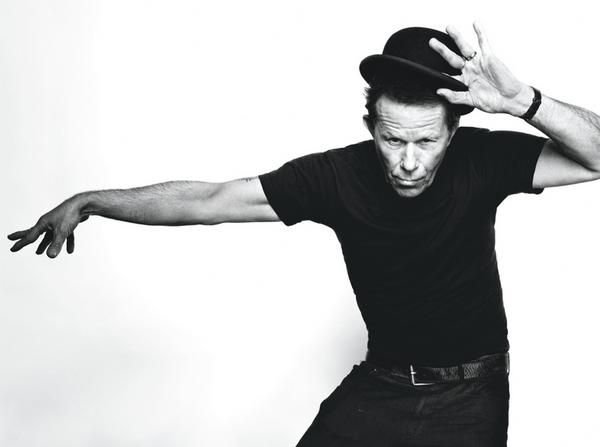 "TOM WAITS has a distinctive voice, described by critic Daniel Durchholz as sounding ""like it was soaked in a vat of bourbon, left hanging in the smokehouse for a few months, and then taken outside and run over with a car. ""With this trademark growl, his incorporation of pre-rock music styles such as blues, jazz, and vaudeville, and experimental tendencies verging on industrial music. Lyrically, Waits' songs frequently present atmospheric portrayals of grotesque, often seedy characters…"