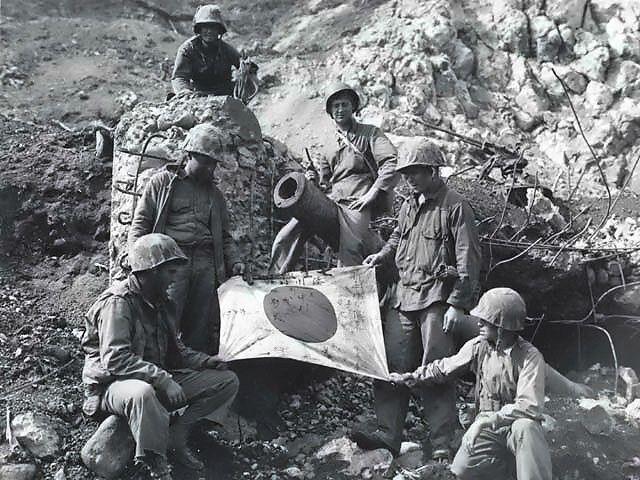 U.S. Marines pose on top of enemy pillbox on Iwo Jima with a captured Japanese flag.