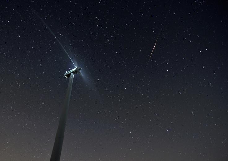 """Título: Qué te metes Don Quijote pa flipar con los molinos  Autor: djmarko  """"Un encuadre diferente a lo habitual, una iluminación oportuna del aerogenerador, un cielo fenomenal y, como culminación, una estrella fugaz que remata la escena. El original encuadre con el aerogenerador inclinado termina de redondear la composición."""""""