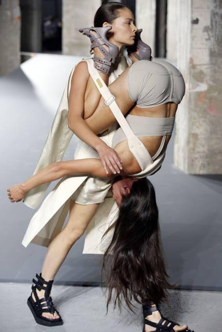 Modelle che «indossano» donne come abiti. Ragazze diverse, quelle di Rick Owens che sfilano a coppie, agganciate, sotto sopra, testa/piedi. La passerella dello stilista statunitense  più che una sfilata sembra uno show del circo. Ogni modella cammina portando addosso un manichino in carne e ossa e sembra un'acrobata  che si sta esibendo (Afp)