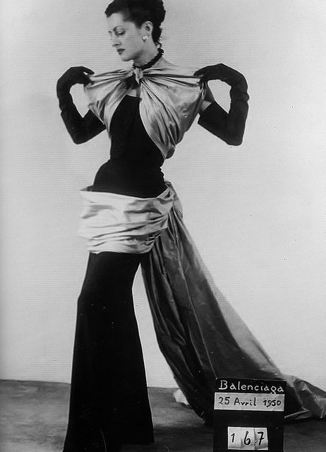 Balenciaga,  April 1950    Evening dress of black wool with taupe silk-shantung draped bodice, hip swag and train.