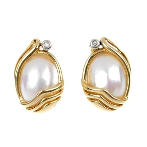 A stunning pair of 9ct gold diamond and mabe pearl earrings.