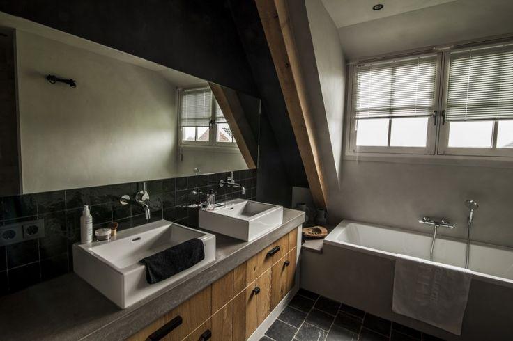 Badkamer met dubbele wastafel met houten accenten op tegelvloer