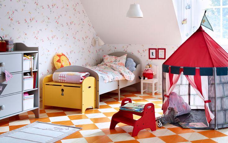 Ein farbenfrohes Kinderzimmer mit hellgrauen ausziehbaren Bett, einer gelben Bank in Form einer Schatzkiste und BEBOELIG Spielzelt