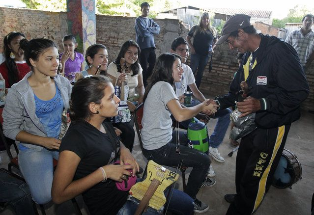 Trash recycler and craftsman Nicolas Gomez (R) greets students of the Orchestra of Recycled Instruments of Cateura, for which Gomez makes all their instruments, in Cateura, near Asuncion, May 9, 2013. The orchestra is the brainchild of its conductor Favio Chavez, who wanted to help the children of garbage pickers at the local landfill, and the instruments are made from salvaged materials by craftsman Gomez. (Photo by Jorge Adorno/Reuters)