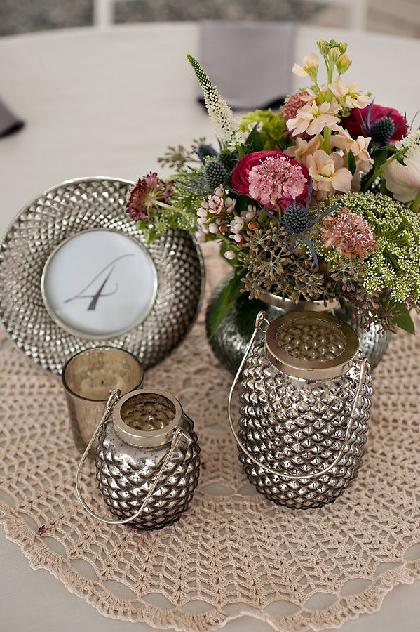 Your centerpieces can be sophisticated and elegant like these grey lantern pieces paired with rustic flowers.
