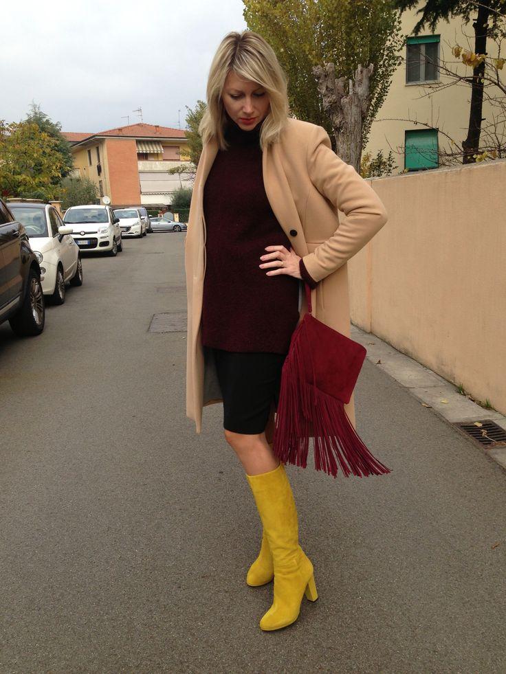 Stivali gialli, maglione bordeaux, cappotto classico beige, borsa a mano con frange