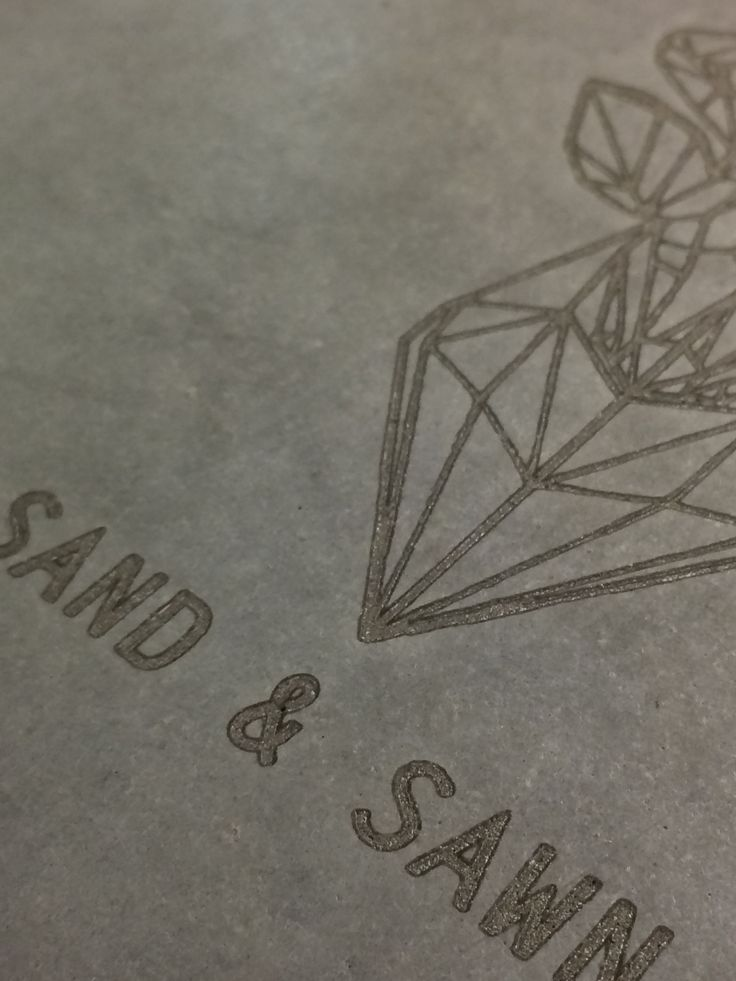 Sand and Sawn Geometric Stag Logo Laser engraved in polished concrete