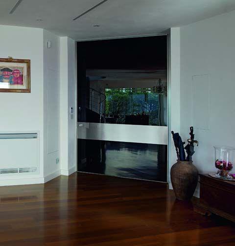 portoncino oikos linea synua anta unica con fascia in acciaio Synua è la porta blindata per le grandi dimensioni con apertura a bilico e complanare al muro. Rivestimento a settori orizzontali. Anta unica fino a 220 cm in larghezza e 300 cm in altezza. Design Adriani&Rossi.