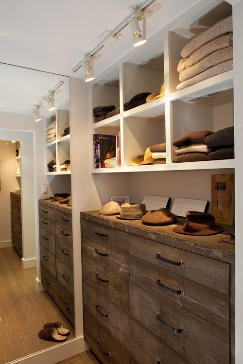 The combination of clean white open storage above the warm color wood fronts of the lower drawers = modern warmth in a fantastic functional closet. Love these built-ins.