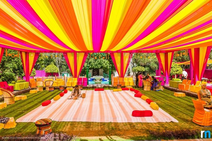 Pink, orange and yellow color coordinated decor with bolsters, matching chair covers- A perfect Mehendi setup. | weddingz.in | India's Largest Wedding Company | Indian Wedding Decor Ideas |