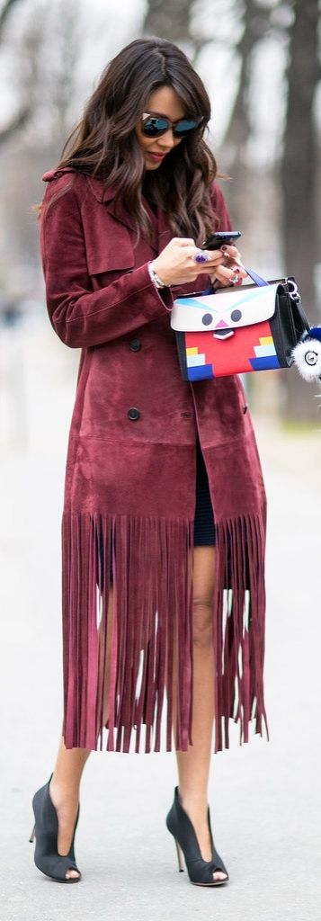 Paris Fashion Week street style inspiration: a wine red fringe suede jacket with a cartoon Fendi purse and black open-toed pumps