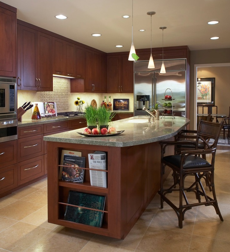 Nice kitchen. I like the island with larger island with the curved front and the bookshelf in the side. Nice cabinets and cabinet color. Good contrast to floor and counter top. Built in appliances look sleek.
