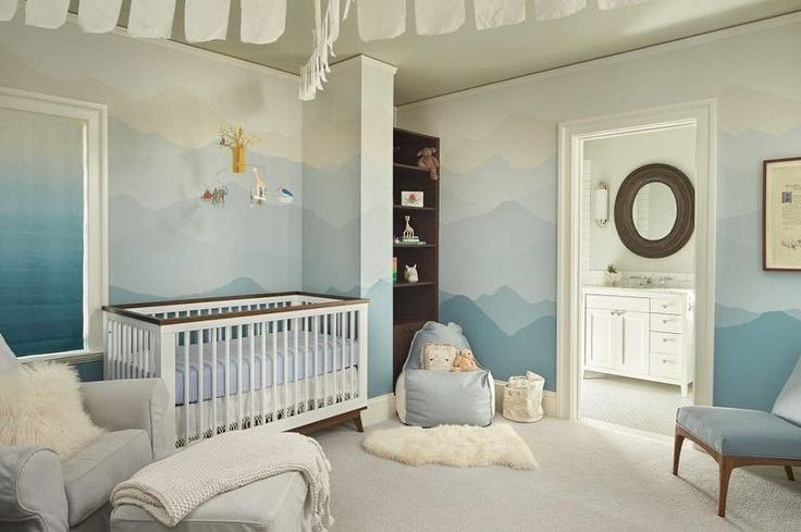 Blue boy's nursery features wall painted ombre blue lined with a two tone crib placed under a safari animal mobile flanked by a gray roll ar slipcovered glider and ottoman to the left and a nook filled with a dark brown bookshelf to the right.