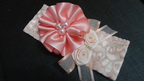 Faixa de renda com elastano larga na cor rosa claro com flor de fita de cetim rosa bebê e rosas com laço de organza rosa claro. Detalhes em pérolas e strass.