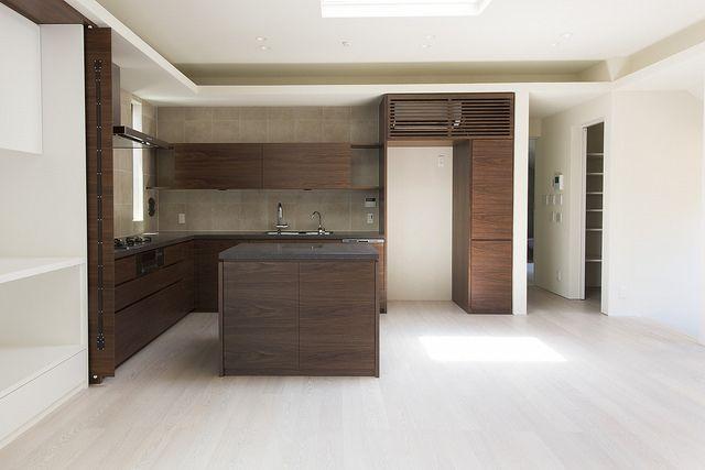 キッチンも収納も空調のルーバーまで、すべてウォルナットでまとめました。つや消しの黒御影の天板が重厚感を際立たせています。