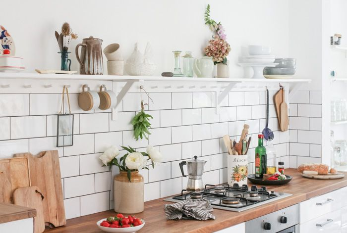 A beautiful modern kitchen, tiled with white metro tiles, and styled with vintage accessories.