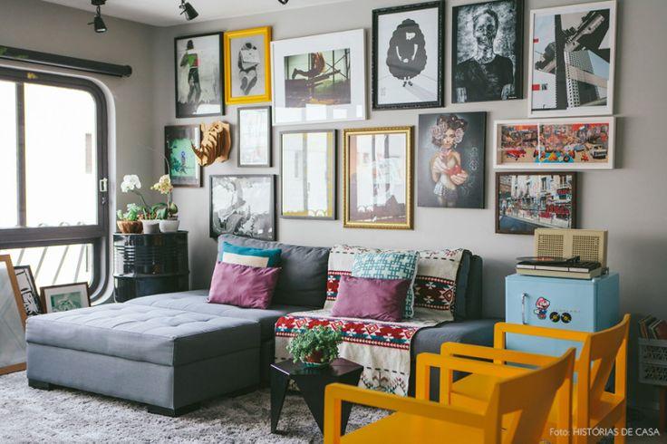 Sala de estar com decoração descolada que inclui parede de quadros, móveis coloridos e muitas plantas.