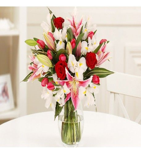 The bright colours in this pretty bouquet sing and delight the eye. Traditional beautiful red roses are arranged with red tulips, elegant white iris with their yellow splashes and are contrasted with the stunning beauty of the large pink Oriental lilies.