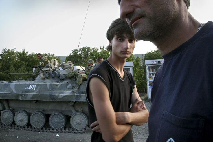 Male residents of the border town of Patara-Garedzhvari stand near a Russian tank. In August, fighting broke out between the Georgian army and separatist forces in the breakaway region of South Ossetia. Russian troops entered the region, which is home to many ethnic Russians, in support of the separatists. As the conflict spread beyond the boundary of South Ossetia, people fled their homes.