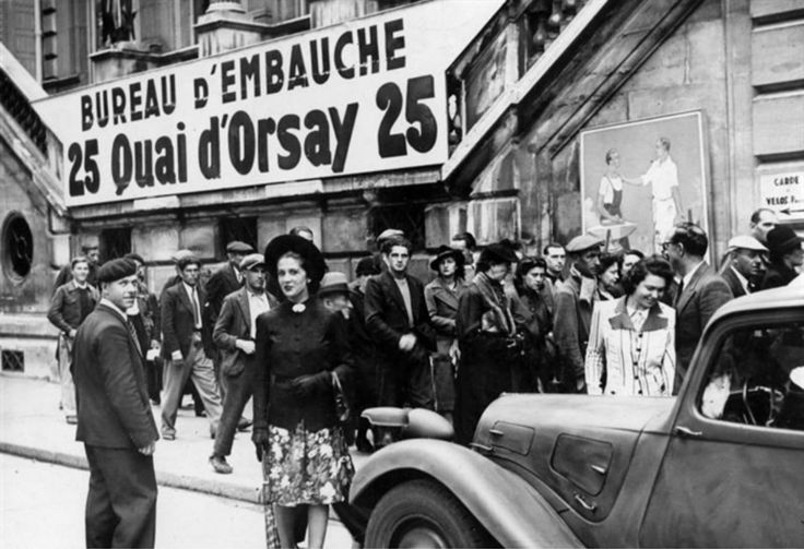 French civilians at the Quai d 'Orsay in German-occupied Paris walk past the sign for a recruitment office for job placement in Germany. Some of the civilians stand in a queue for prospective work. Most French workers in Germany were forced laborers...