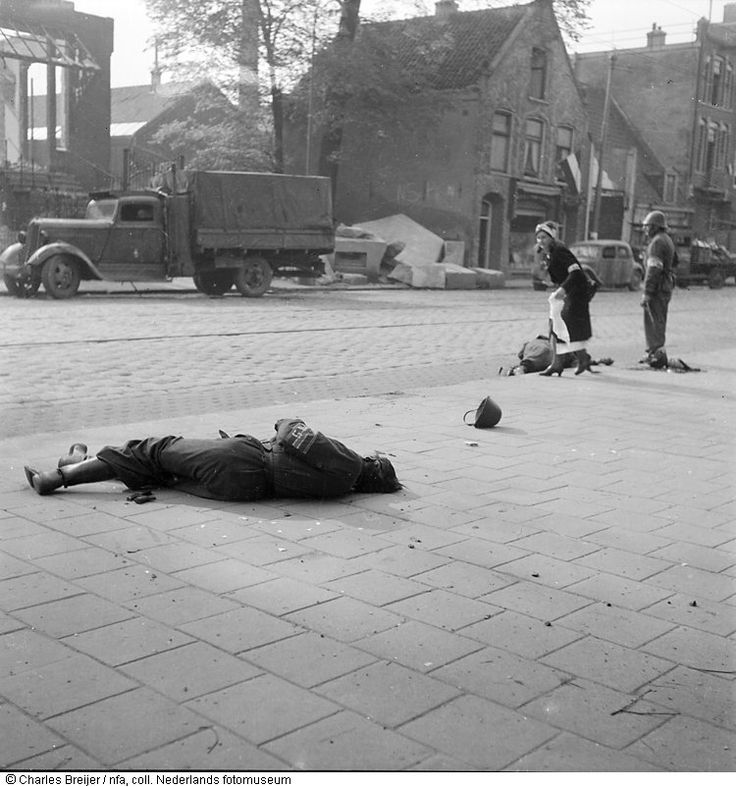 Injured fighters of the Dutch Underground Army (NBS) lie in the street during end-of-war skirmishes on May 7, 1945. A Red Cross worker is trying to offer first aid, while another NBS member is standing next to her. The Germans beat a hasty retreat from the Netherlands but couldn't avoid leaving behind numerous POWs. #amsterdam #worldwar2