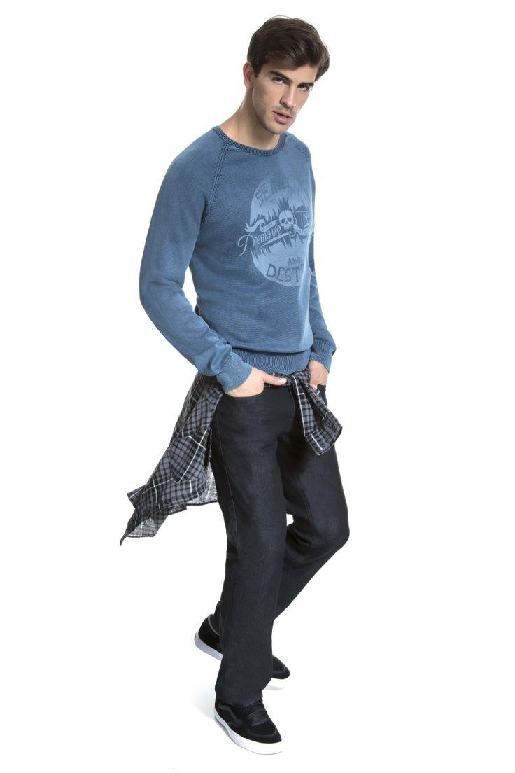 Tricô azul lavado e estampado, camisa xadrez monocromática amarrada na cintura e calça jeans escura.