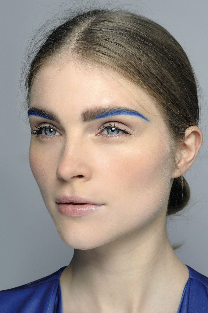 COLOURED BROWS -- Minimal skin, eyes and lips paired with a line of blue brows underneath the brow and blended in with the body of brow.