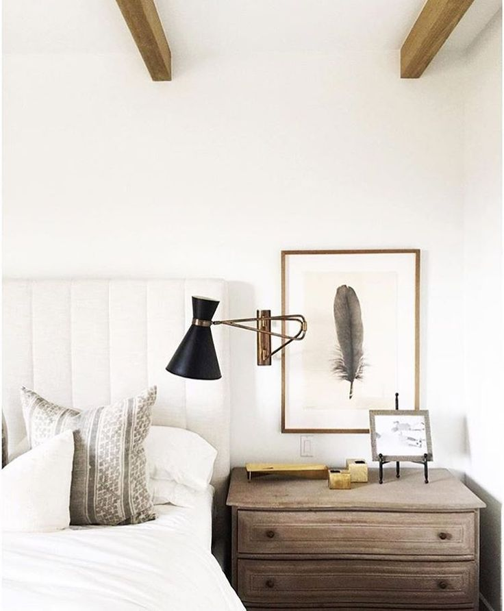 Minimalist bedroom- white walls, white upholstered headboard, sconce, side table and art hanging above it