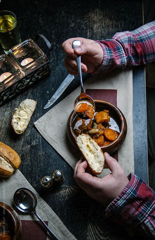 Rustic table setting with a mans hand eating a bowl of soup with bread.#food #photography #stock #stocksy.