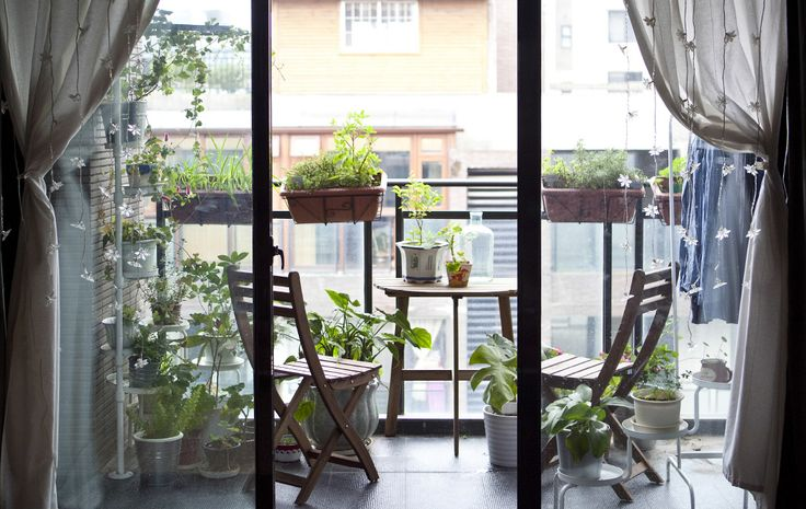 Space-efficient folding furniture lets Justin use his balcony for multiple purposes, houseplants, patio ideas.