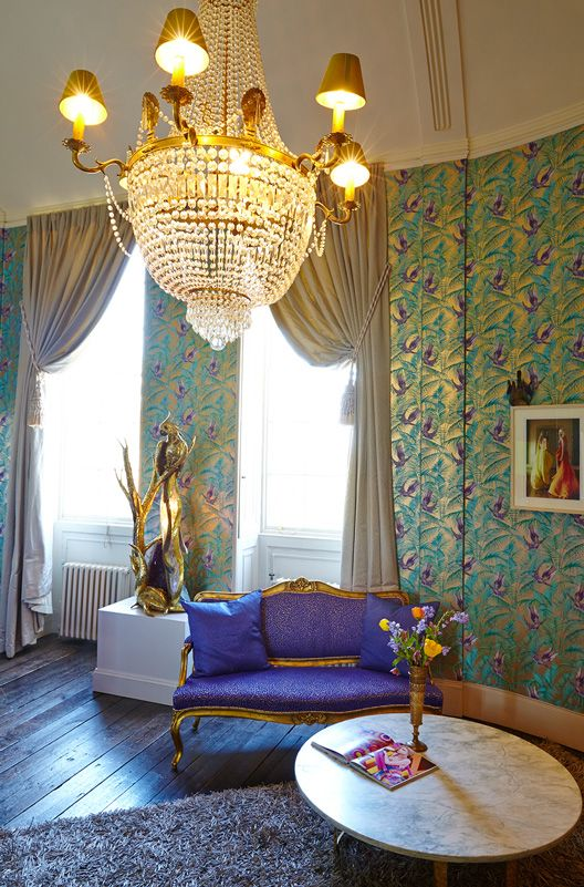 The bridal suite designed by Matthew Williamson at Aynhoe Park features an upholstered couch in purple Ocelot fabric with a gold parrot statue. The suite's walls are covered in metallic Osborne and Little sunbird wallpaper and feature high ceiling windows with draping curtains. A marble coffee table is placed in front of the couch with flowers and magazines as decoration.