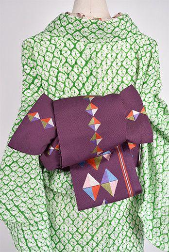 おだやかな紫色の地に、オルテガデザインを思わせる菱の飾り模様が織り出された半幅帯です。