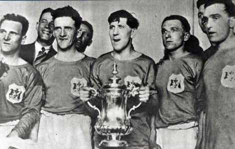 Fred Keenor holds the FA Cup with his Cardiff City team-mates after their famous win over Arsenal in 1927