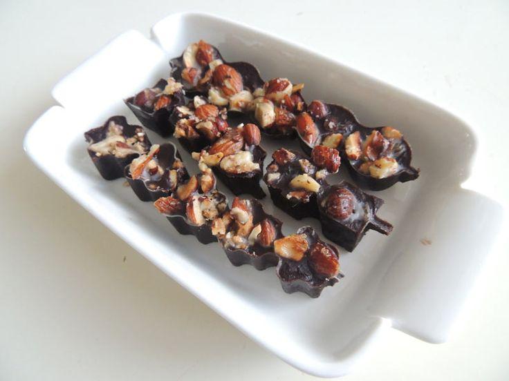 PALEO: 3 eetlepels kokosolie 2 eetlepels cacao 1 volle eetlepel ahornsiroop, agavesiroop of honing (varierend hoe puur of zoet je het wil hebben) 12 hazelnoten, 12 amandelen, 12 rozijnen. Hak noten grof en rooster in de pan. smelt cocosolie en voeg dan siroop en cacao toe. doe in vormpjes en strooi de noten erover. Uitharden