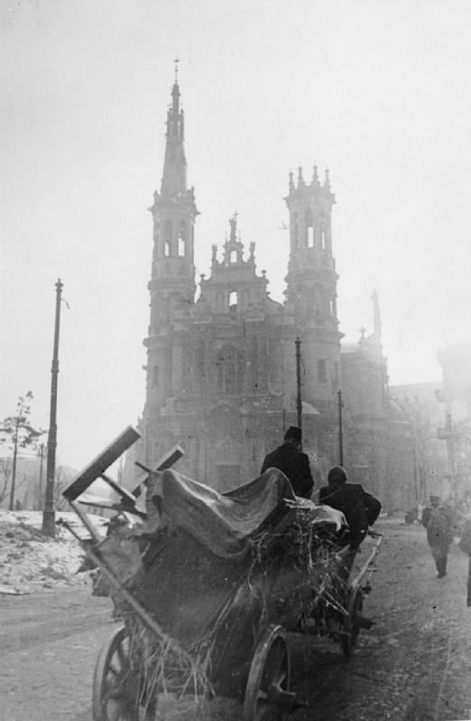 WARSAW CITIZENS RETURN, FEBRUARY, 1945; Residents of Warsaw pull a large cart loaded with their belongings as they return to their homes following the liberation of the city by the Red Army. A large ornate building, perhaps a church, can be seen through the mist.