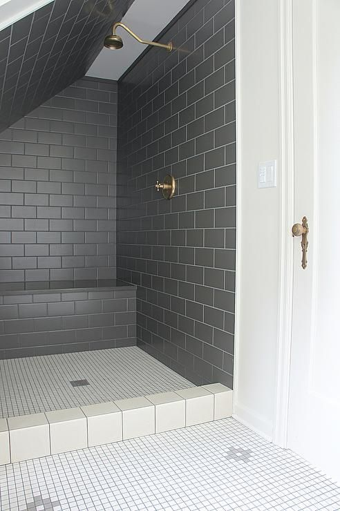 Clad in black subway tiles, sloped shower features a tiled bench, a vintage brass gooseneck shower head, and white grid floor tiles.
