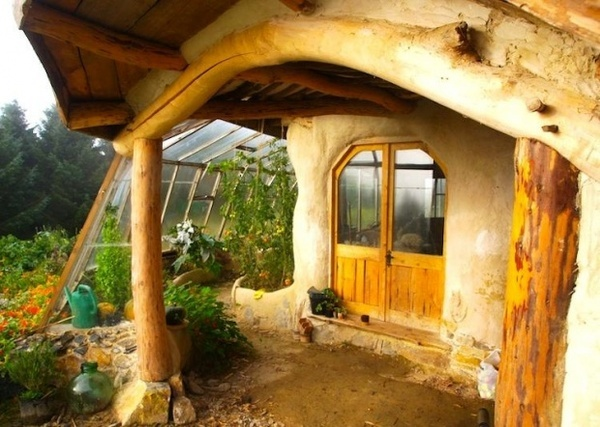 eco-friendly house and greenhouse. Adding glass porches and greenhouse/conservatory to entry/exits cuts down draughts and heatloss, increases your insulation and growing season!