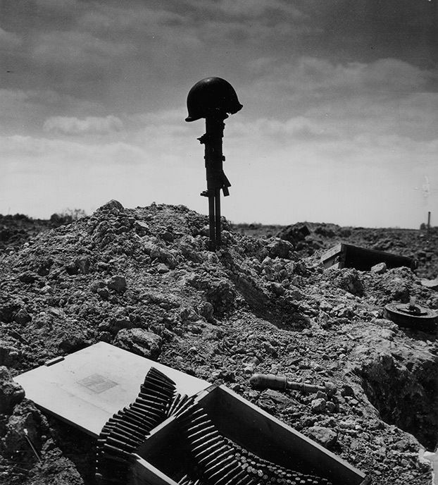 warisstupid:  A makeshift grave for a fallen GI amid machinegun ammo, an antitank mine, and more war debris. The brave fallen warriors of the D-Day invasion and Normandy campaign shall never be forgotten. Image Credit: Conseil Régional de Basse-Normandie / National Archives USA