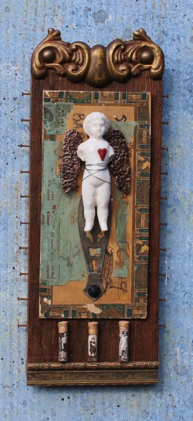 A beautiful frozen charlotte doll that has been rescued and repurposed, her wings are hammered copper, the background a vintage cigar box lid and three glass vials with pictures of sweet children inside. Measures: 11 tall 5 wide at nails 2 deep at body. Designed to hang on wall, hardware