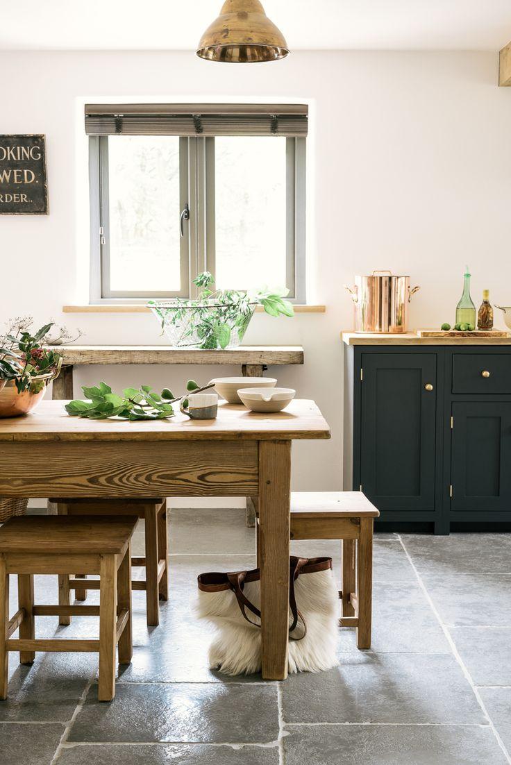 dark blue deVOL cupboards, brass hardware, brass pendant lights and antique furniture make for a pretty perfect kitchen