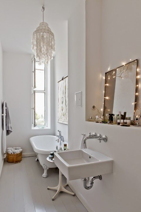 a cool white bathroom, which is so simple I love it. But the thing that really catches my attention are those so so cute fairy lights around the mirror. Shows what simple touches can do...