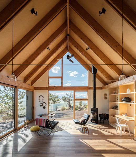Modern home with living room, chair, coffee tables, medium hardwood floor, ceiling lighting, and wood burning fireplace. Photo 5 of Big Cabin | Little Cabin