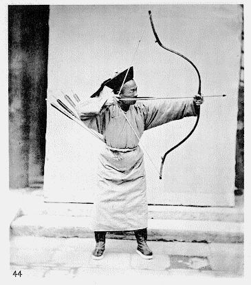 The picture is most likely posed, or otherwise the archer uses an alternative grip in order to hold the bow long enough for the shot. With the technology John Thomson had available the exposure time would be seconds in summer, but much longer in winter due to the delayed effect of the chemicals at work.  Both his bow and string hand are not how they are supposed to be.   The overall posture seems to be correct though, so the man may have actually known how to shoot, circa 1865.