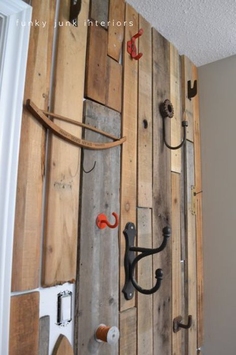 Cool use of pallet wood for the wall covering. It has space between so the white wall behind can show through. But the wood itself covers most. Then the hook become all kinds of things that can hang things. The odder the better. Personally, a bale hook would look right at home. A corn hook, too...