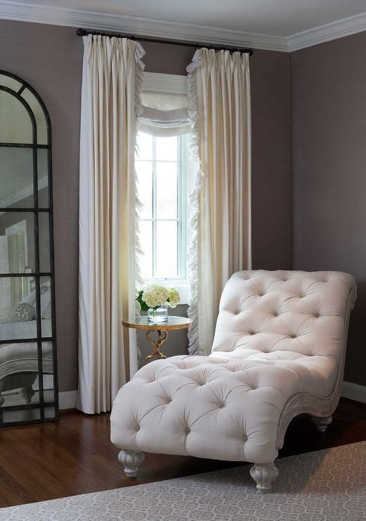 Elegant bedroom features a linen tufted French chaise lounge next to a brass quatrefoil table, Regina Andrew Pattern Makers Cigar Table, placed in front of a window dressed in cream ruffled curtains next to an arched French floor mirror.