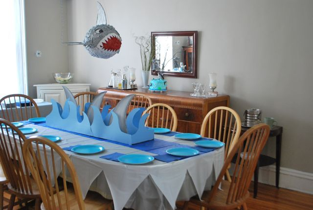 Paper waves and cardboard shark fins a cute centerpiece make.  Oh, and loving the shark-toothed tablecloth.